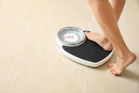 Frau, die drinnen auf Bodenwaagen tritt, Platz für Text. Übergewichtsproblem Standard-Bild