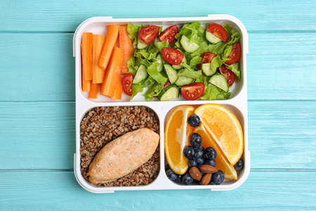 Tray with healthy food for school child on light blue table, top view