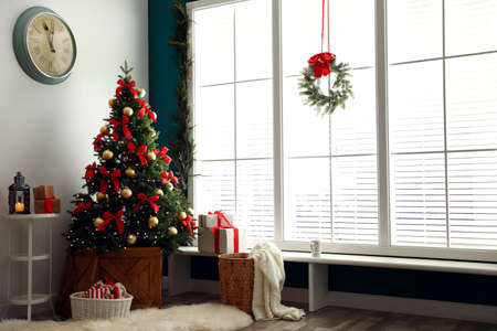 Stylish room interior with decorated Christmas tree<a href=