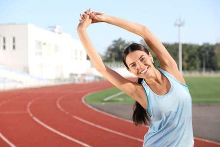 Young sportswoman with wireless earphones stretching at stadium Standard-Bild - 133238444