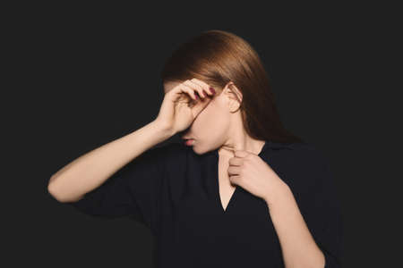 Upset young woman crying against dark background
