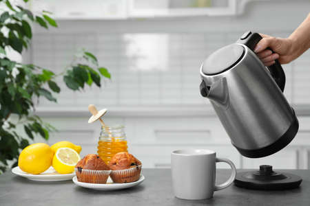 Woman pouring water from modern electric kettle into cup at grey table in kitchen, closeup