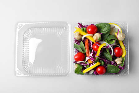 Plastic container with fresh salad on white background, top view