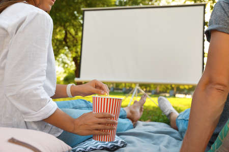 Couple with popcorn watching movie in open air cinema, closeup. Space for text