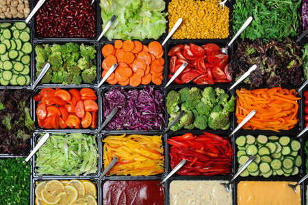 Salad bar with different fresh ingredients as background, top view
