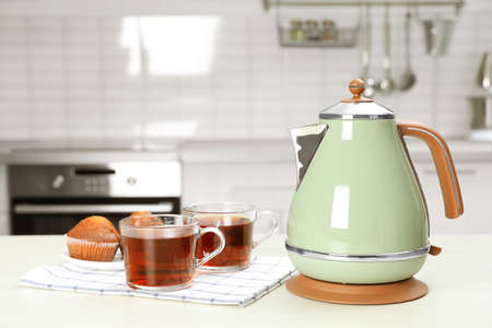 Modern electric kettle, cups of tea and muffins on white wooden table in kitchen. Space for text