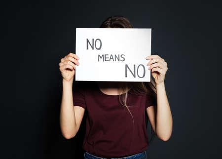 Giovane donna che tiene la carta con le parole NO SIGNIFICA NO su sfondo scuro Archivio Fotografico