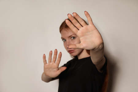 Young woman making stop gesture against light background, focus on hand 写真素材