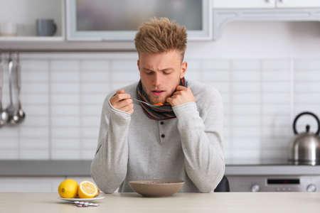 Kranker junger Mann, der Suppe isst, um Grippe am Tisch in der Küche zu heilen? Standard-Bild