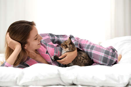 Woman with cat in bedroom. Owner and pet