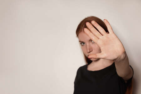 Young woman making stop gesture against light background, focus on hand. Space for text 写真素材