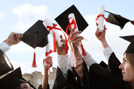 Group of students with diplomas outdoors. Graduation ceremony