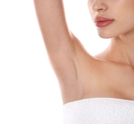 Giovane donna che mostra l'ascella su sfondo bianco, primo piano. Procedura di epilazione