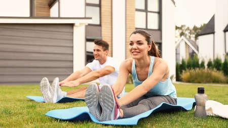 Pareja deportiva practicando yoga matutino en el patio trasero. Estilo de vida saludable