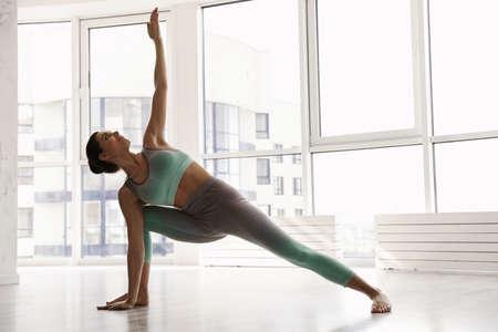 Young woman practicing extended side angle asana in yoga studio. Utthita Parsvakonasana pose Stock fotó