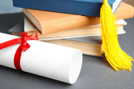 Graduation hat, books and student's diploma on grey table, closeup