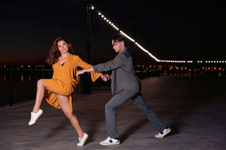 Beautiful young couple practicing dance moves in evening outdoors Banque d'images