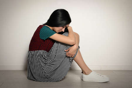 Upset young woman sitting on floor near light wall