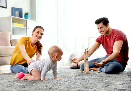 Entzückendes kleines Baby, das zu Hause in der Nähe der Eltern krabbelt