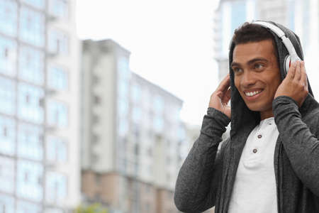 Handsome young African-American man with headphones listening to music on city street. Space for text Standard-Bild - 133239512