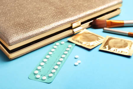Birth control pills and condoms near clutch on light blue background. Safe sex concept Stock Photo