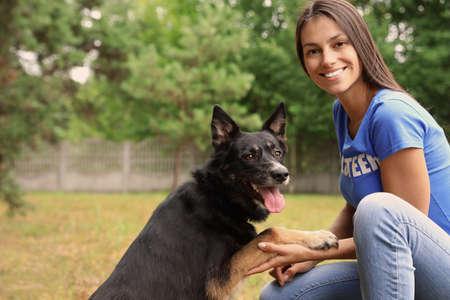 Female volunteer holding dog's paw at animal shelter outdoors Stock Photo
