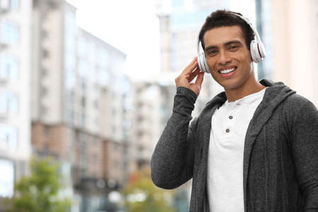 Handsome young African-American man with headphones listening to music on city street. Space for text Standard-Bild - 133239540