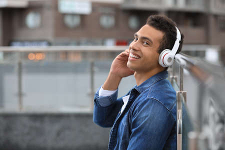 Handsome young African-American man with headphones listening to music on city street. Space for text Standard-Bild - 133239543