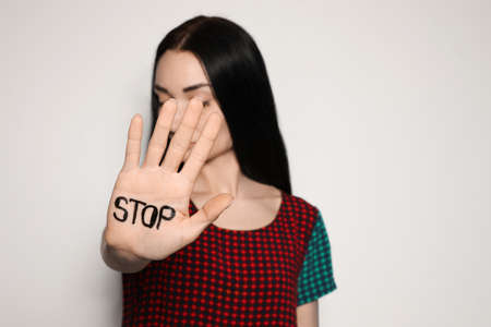 Young woman with word STOP written on her palm against light background, focus on hand. Space for text