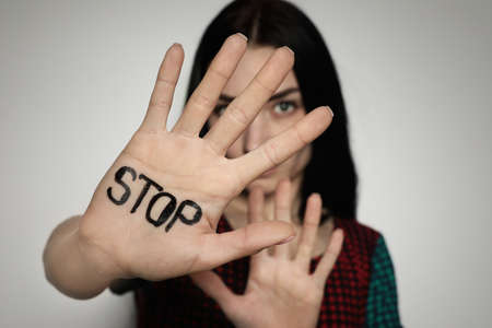 Young woman with word STOP written on her palm against light background, focus on hand Stock Photo