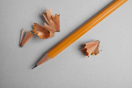 Pencil and shavings on grey background, top view