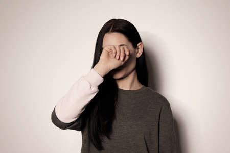 Young woman covering face against light background Фото со стока