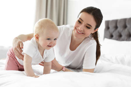 Adorable little baby crawling near mother on bed indoors Imagens