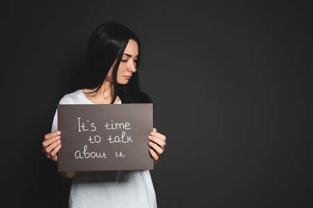 Młoda kobieta trzyma kartę ze słowami nadszedł czas, aby o tym porozmawiać na ciemnym tle. Miejsce na tekst