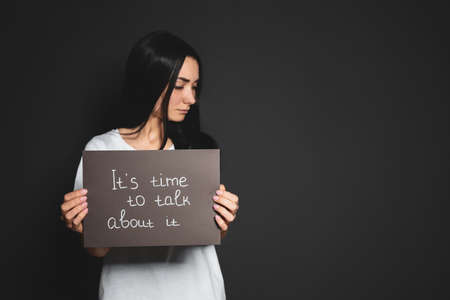 Tarjeta de explotación de mujer joven con palabras es hora de hablar sobre el fondo oscuro. Espacio para texto