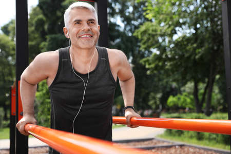Handsome mature man doing exercise on sports ground, space for text. Healthy lifestyle