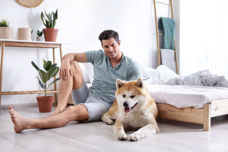 Man and Akita Inu dog in bedroom decorated with houseplants Stock Photo