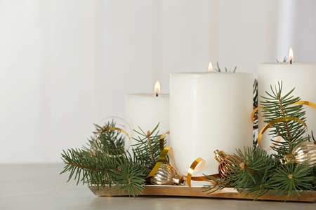 Beautiful Christmas composition with burning white candles on grey table. Space for text Stockfoto