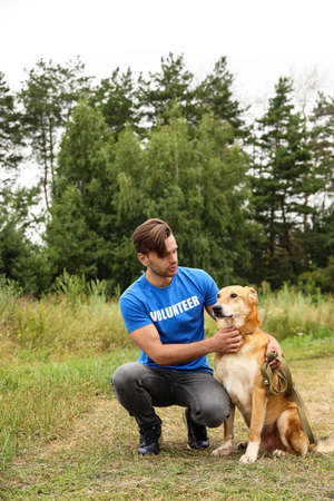 Male volunteer with homeless dog at animal shelter outdoors
