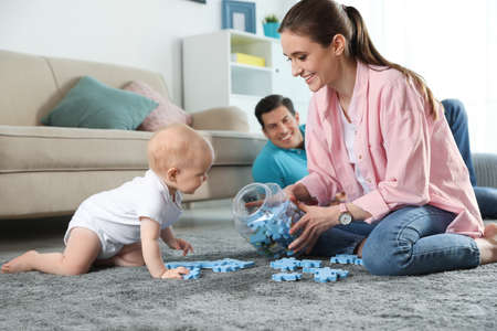 Happy mother playing with little baby on floor indoors Reklamní fotografie