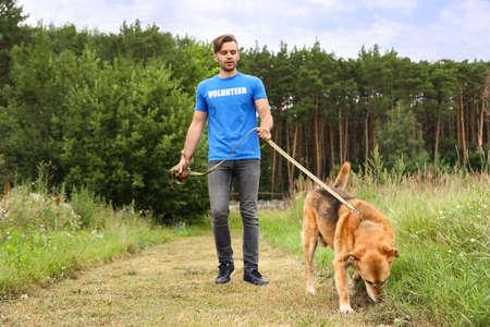 Volontario maschio con cane senzatetto al rifugio per animali all'aperto