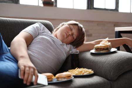 Garçon en surpoids dormant sur un canapé entouré de restauration rapide Banque d'images