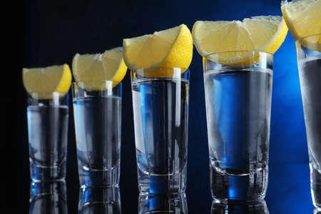 Shot glasses of vodka with lemon slices on dark blue background Standard-Bild