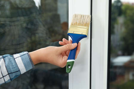 Woman painting window frame at home, closeup