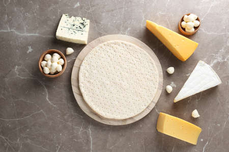 Flat lay composition with pizza crust and fresh ingredients on table