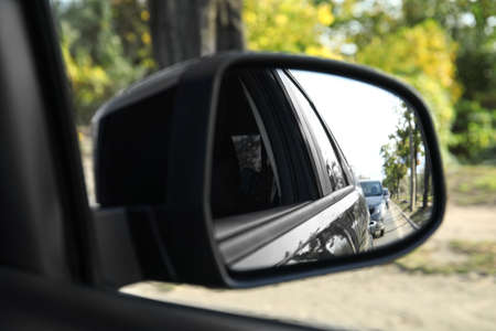 Closeup of car side rear view mirror on sunny day
