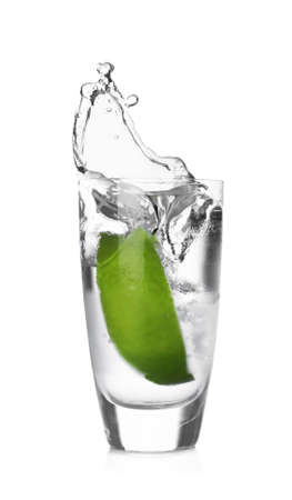 Lime slice falling into shot glass of vodka on white background