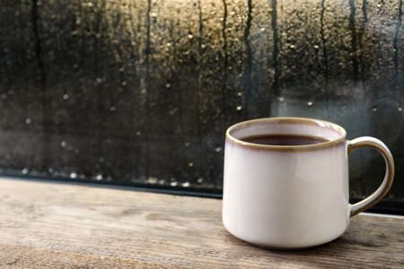 Cup of hot tea on wooden window sill. space for text. Rainy weather