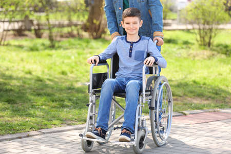 Preteen boy in wheelchair with his father at park on sunny day Reklamní fotografie