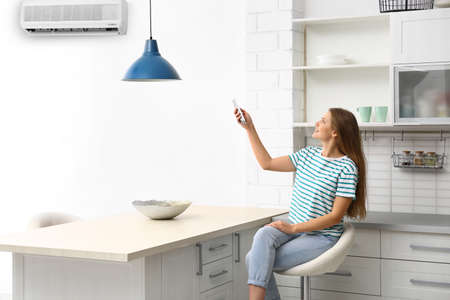 Young woman with air conditioner remote control at home Stockfoto